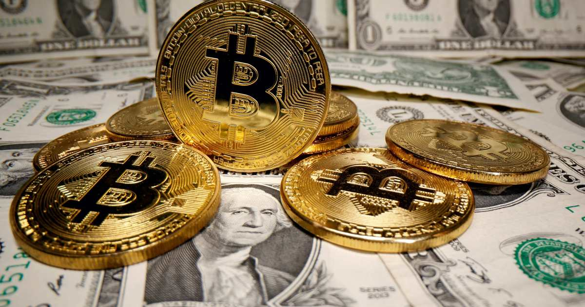 Picture of four bitcoins on a floor covered with U.S. dollar currencies