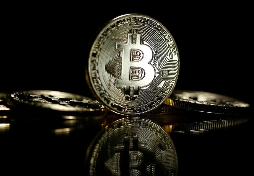 Picture of a standing bitcoin with two bitcoins lying on either side of it, with a black background