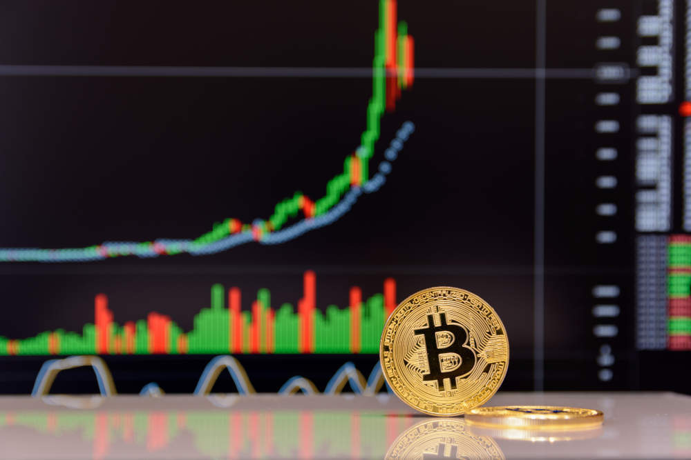 Picture of a bitcoin standing in front of a chart in an upward trend