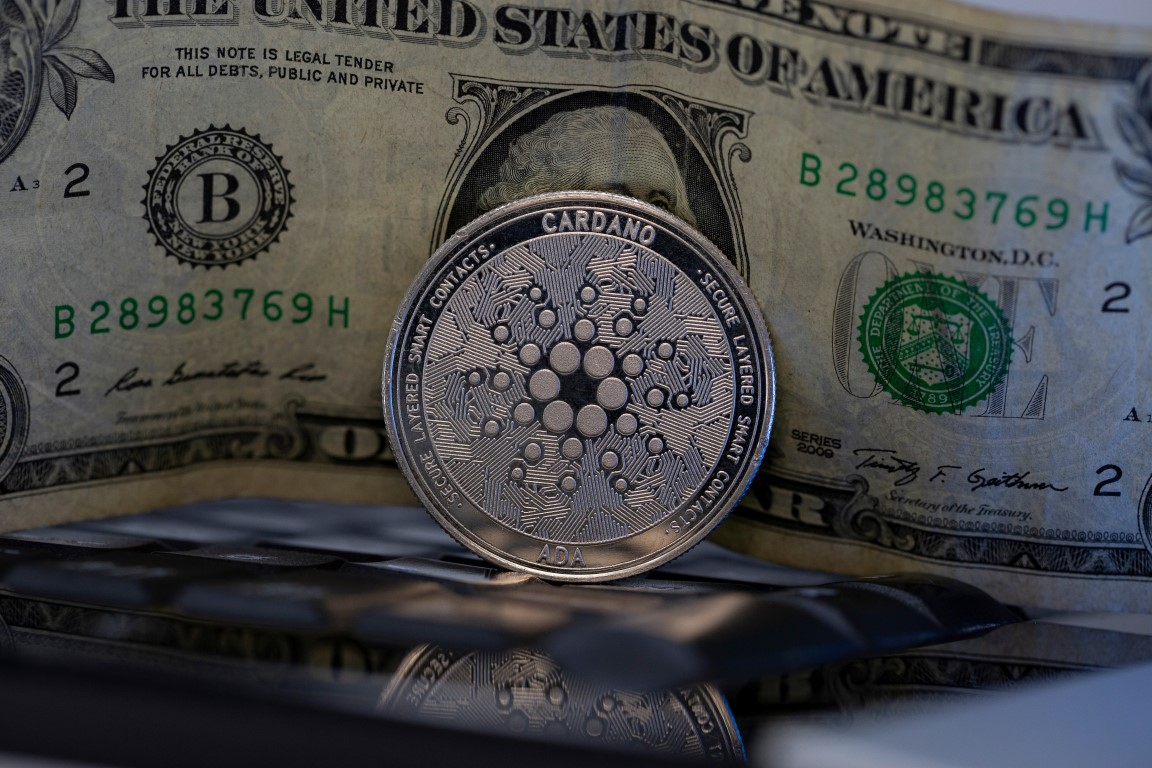 Picture of a Cardano coin standing in front of a U.S. dollar bill