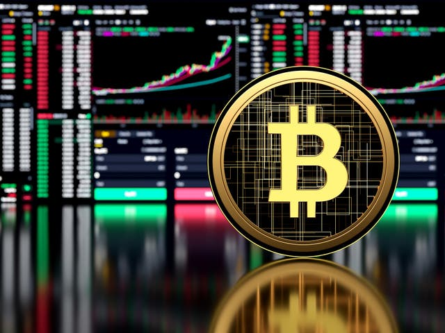 Picture of a bitcoin standing in front of various market charts